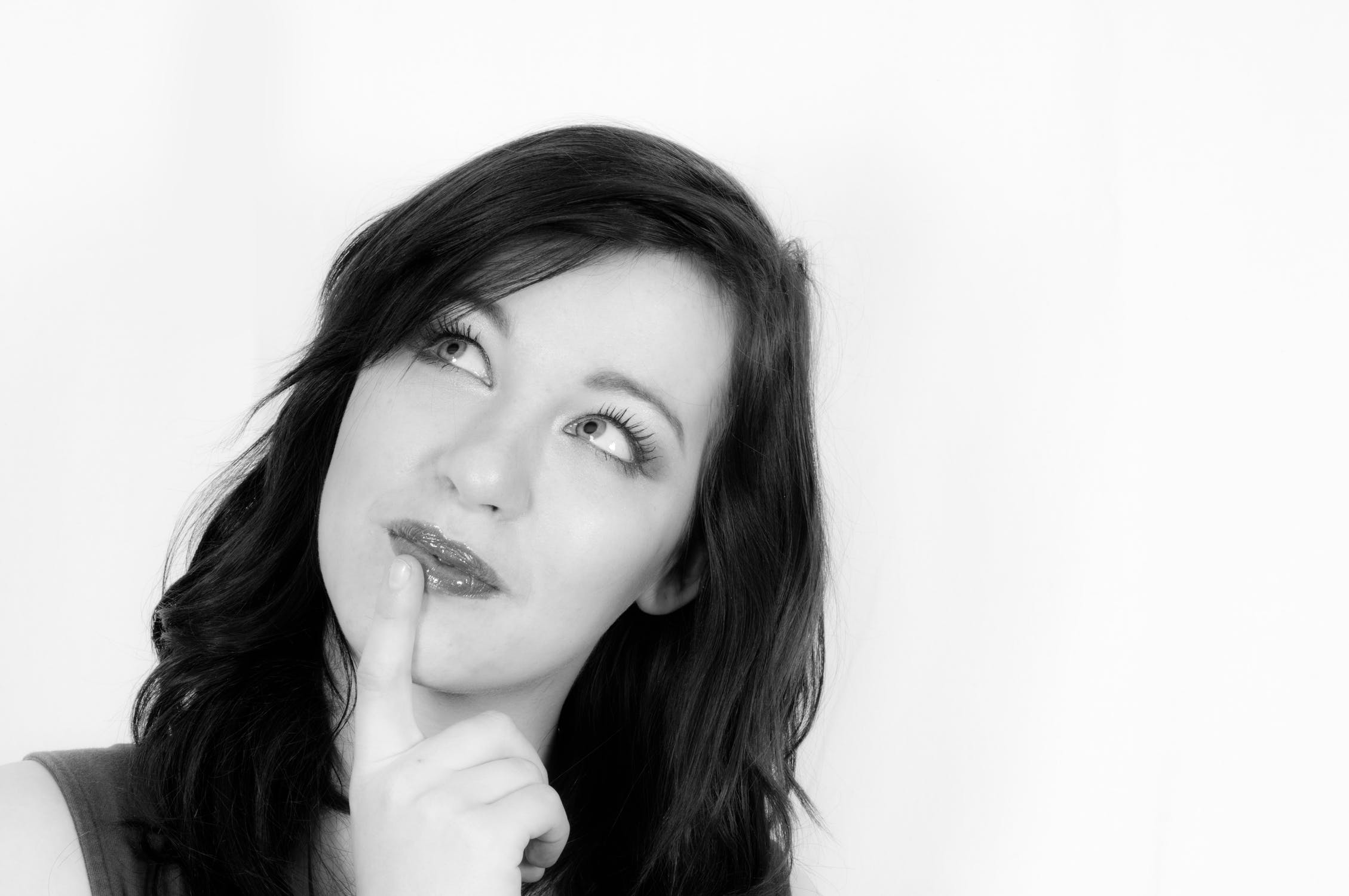 Girl thinking with finger on lip
